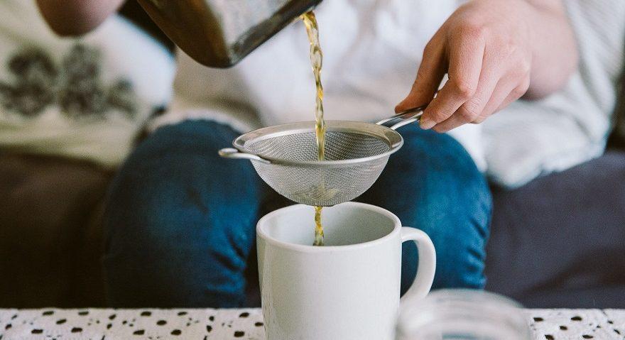 pouring tea through tea strainer