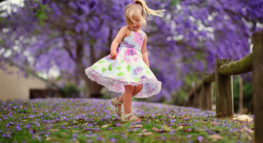 small girl in leaves during spring
